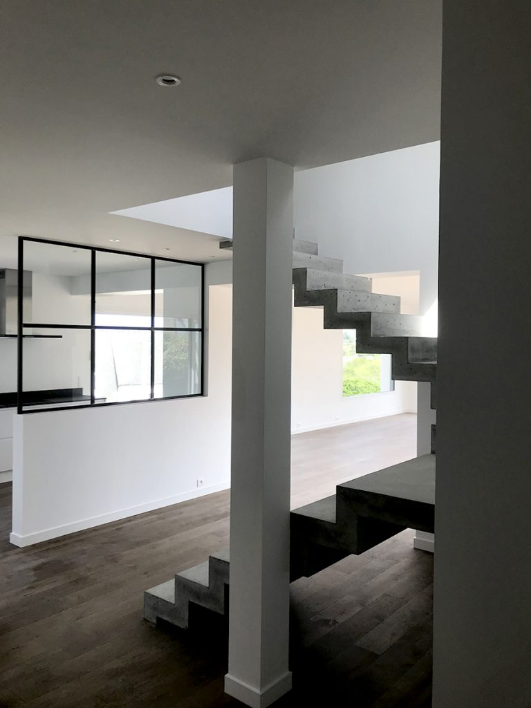 La maison est équipée d'un escalier architectural en béton.