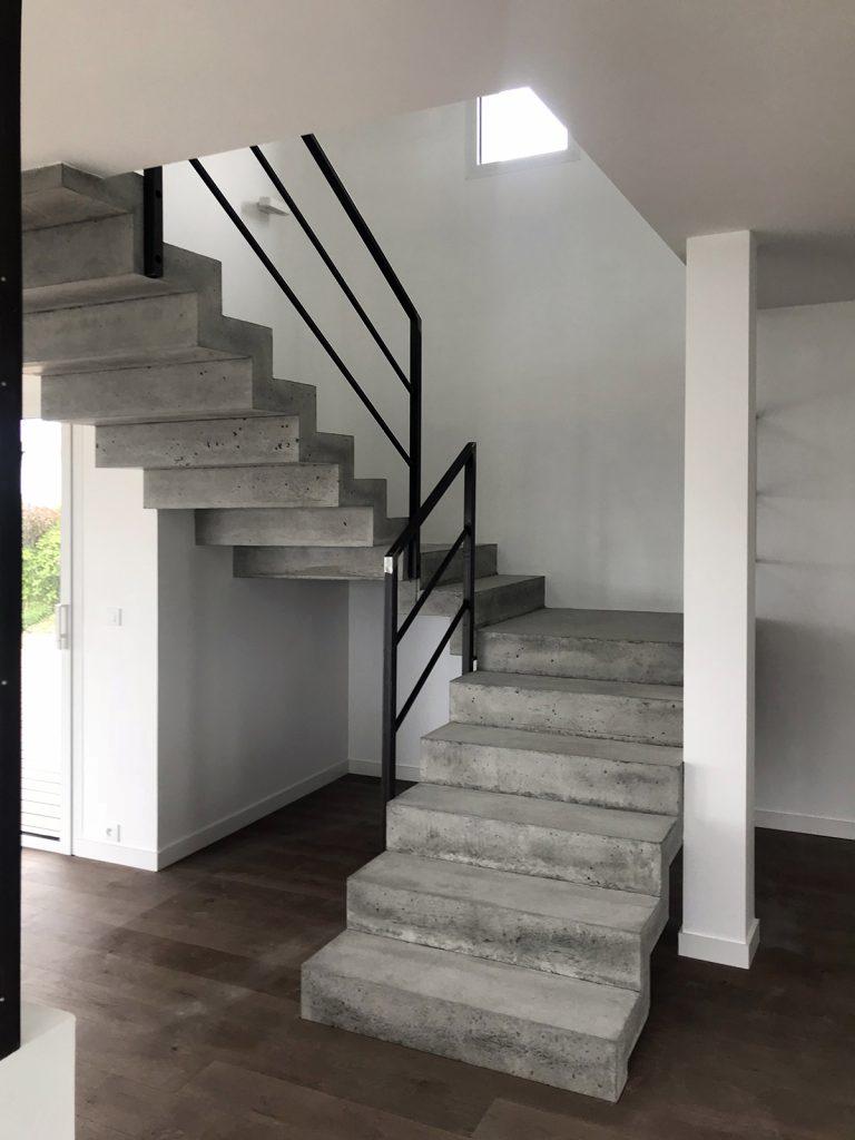 Le rez de chaussé est équipé d'un sol parquet et l'escalier vers l'étage est en béton