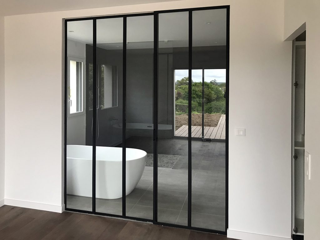 Une belle verrerie industrielle en acier équipe la salle de bain de cette maison à Carantec