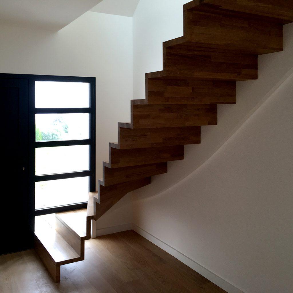 Magnifique escalier en bois type piano à l'entrée de la maison.
