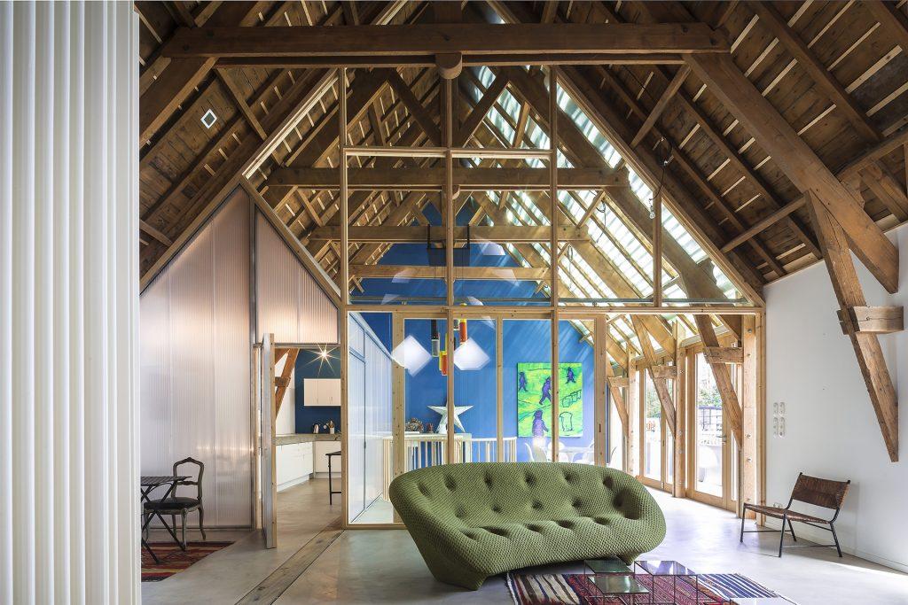 La charpente en pin a été conservée et percée pour crée une baie vitrée et couvert d'ardoise et ardoise de verre.